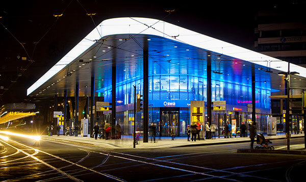 Das Haltestellendreieck am Königsplatz hell erleuchtet bei Nacht.