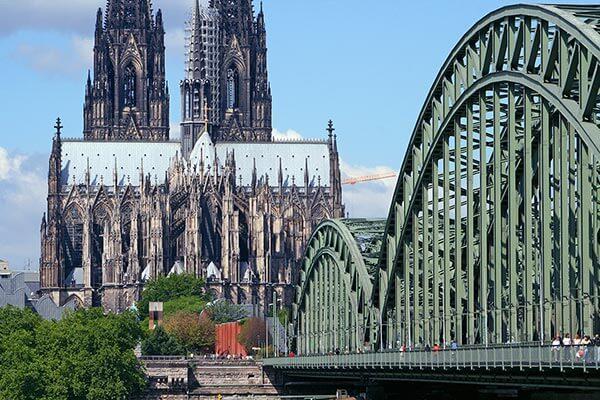 Der Dom als Wahrzeichen der Stadt Köln. Die Hohenzollernbrücke im Vordergrund ist eine der meistbefahrenen Eisenbahnbrücken in Deutschland.