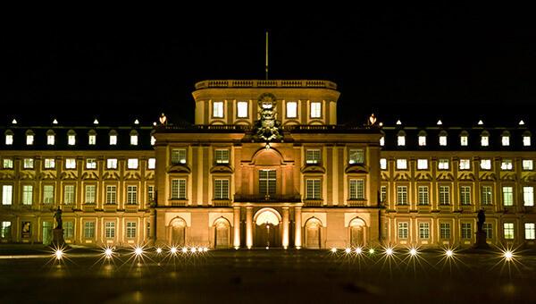 Der Mittelbau von Schloss Mannheim prachtvoll erleuchtet bei Nacht.