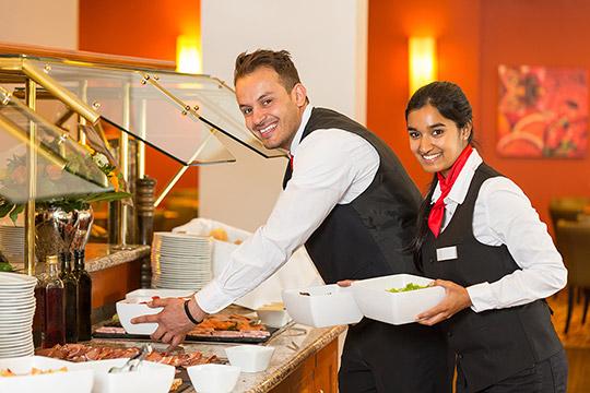 Bild Nebenjob als Frühstückskraft – Frühstückskräfte beim Aufbauen des Frühstücksbuffets.