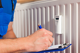 Bild Nebenjob als Heizungsableser – Heizungsableser notiert den Zählerstand eines elektronischen Heizkostenverteilers.