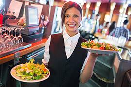 Bild Nebenjob als Kellner / Servicekraft – Kellnerin beim Servieren von Salaten in einem Restaurant.