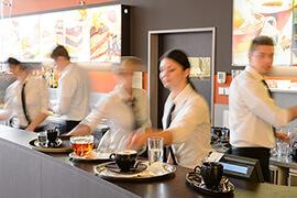 Kellnerinnen und Kellner bei der Zubereitung von Getränken in einem Café.